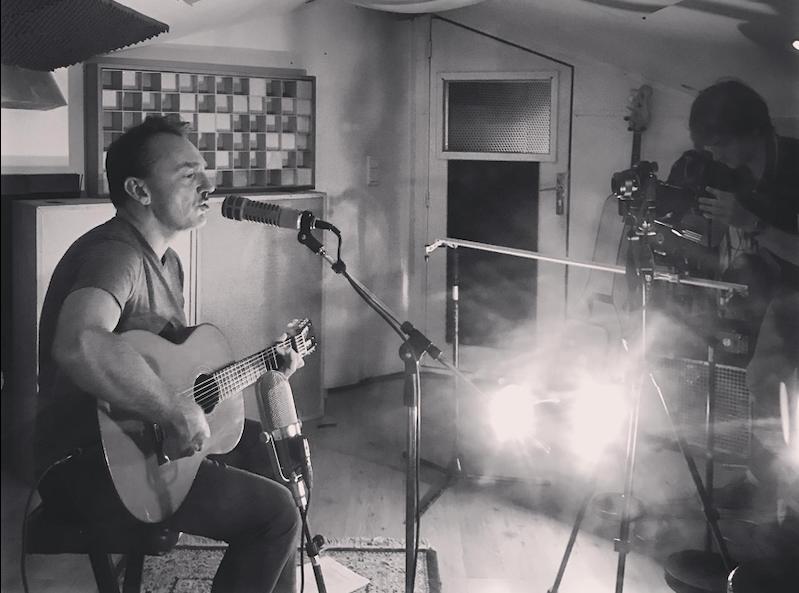 Artiste chanteur et guitariste enregistrant une chanson dans un studio d'enregistrement. @ Milos Asian - Kitchen Studio