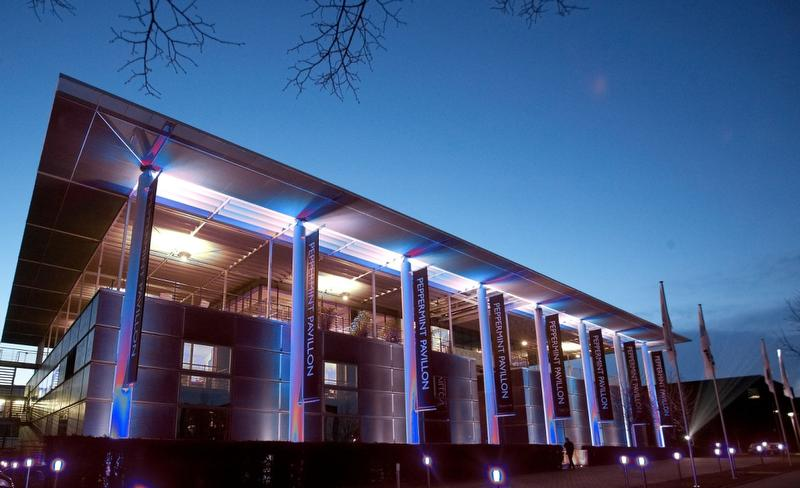 Peppermint Park Studios : stade avec des éclairages lumineux roses et bleus la nuit